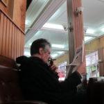 Reading paper with cigar in Cafe de Paris