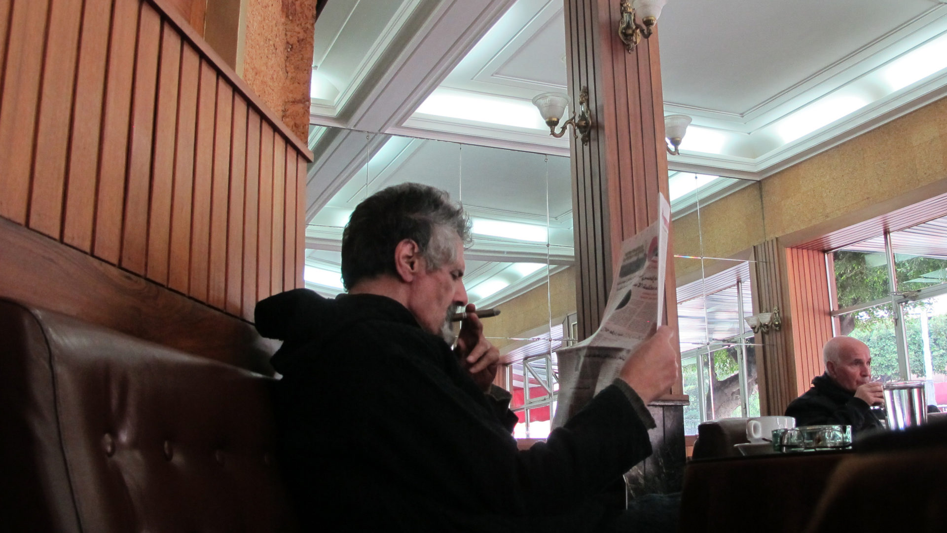 Reading paper with cigar in Cafe de Paris