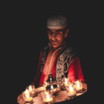 Bashir holding a tray of candles. Photograph by Will Rijnbout.